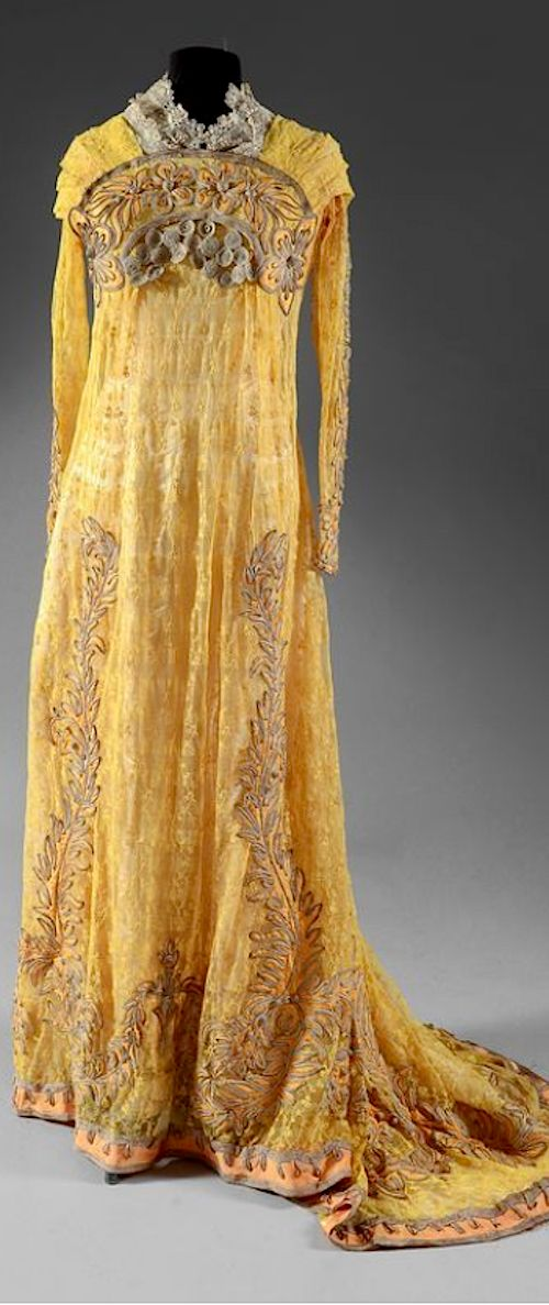 Tea gown, around 1910 . Coutau-Begarie pictures  tulle embroidered with lemon yellow florets, cream satin dress background. High-waisted, long-sleeved bodice, pleated panel underlined with a stylized arch in silver soutache and satin appliqué. Flared skirt with long train embroidered with flippers and festoons, (small holes in satin). Estimate : 700 / 1,000 €