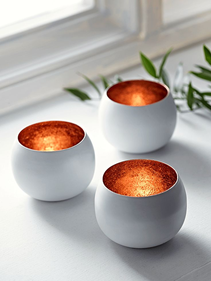 Inspired by our bestselling White & Copper Pendant Light and White & Copper Bowl, our set of three petite tea light holders has a matt, soft white finish on the exterior and a copper leaf effect on the inside.   The flicker of your tea light flame will be further enhanced but the metallic interior, lending a warm glow to the atmosphere in your room.