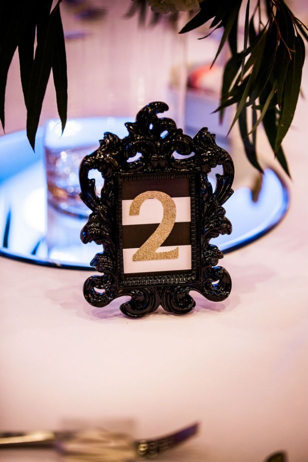 Modern glam wedding table numbers with gold glitter, black and white stripes, and a painted black frame to tie it all together (Photo by Asteria Photography)