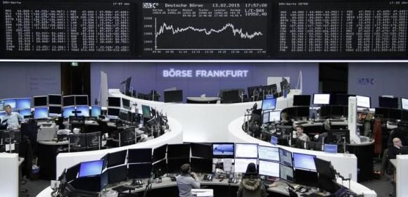 Traders are pictured at their desks in front of the DAX board at the Frankfurt stock exchange February 13, 2015.     REUTERS/Remote/Staff