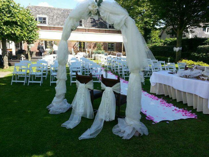 Decoratie van een trouwceremonie: super romantische boog met echte bruidsstoelen.