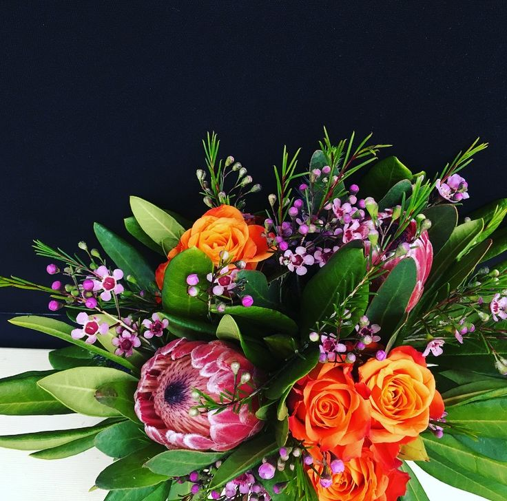 Table centerpiece by Bettie bee blooms. Wax flower, orange/red roses, pink ice protea.