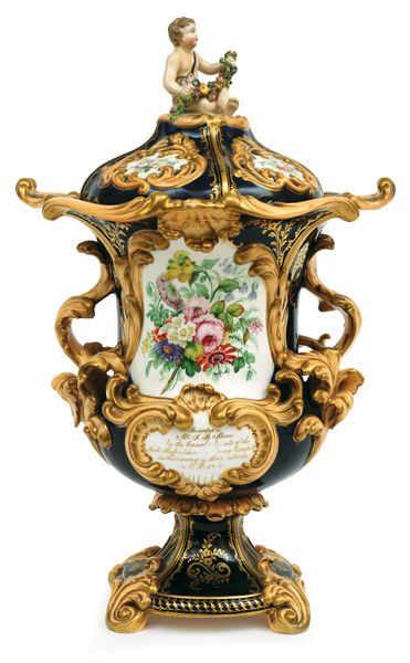 Coalport porcelain presentation vase, circa 1860, the footed trumpet shaped vase with acanthus handles and pierced sectional cover and figural finial, heavily moulded throughout with gilded foliate flourishes framing hand painted floral cartouches and with a further hand scripted dedication panel to the lower front,