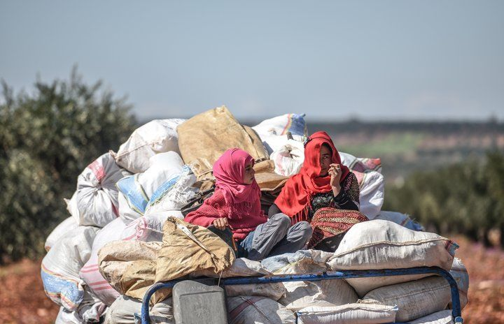 Syrian women arrive at a checkpoint in the village of Anab ahead of crossing to the Turkish-backed Syrian rebels side on March 17, 2018 as civilian flee the city of Afrin in Northern Syria.