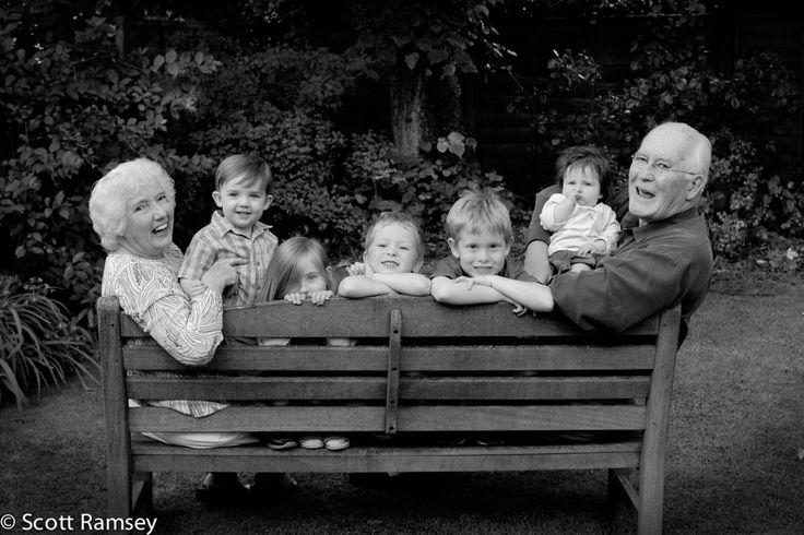 Grandparents and their grandchildren sitting on a garden bench in Epsom, Surrey.