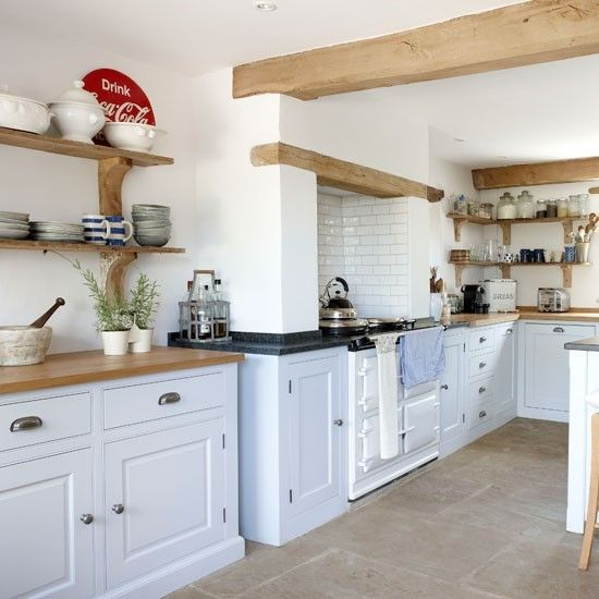 In a classic country colour combination, pale blue Shaker-style units team up with pristine white walls and a white range cooker. Add warmth with worktops and wall shelves in light-toned wood.