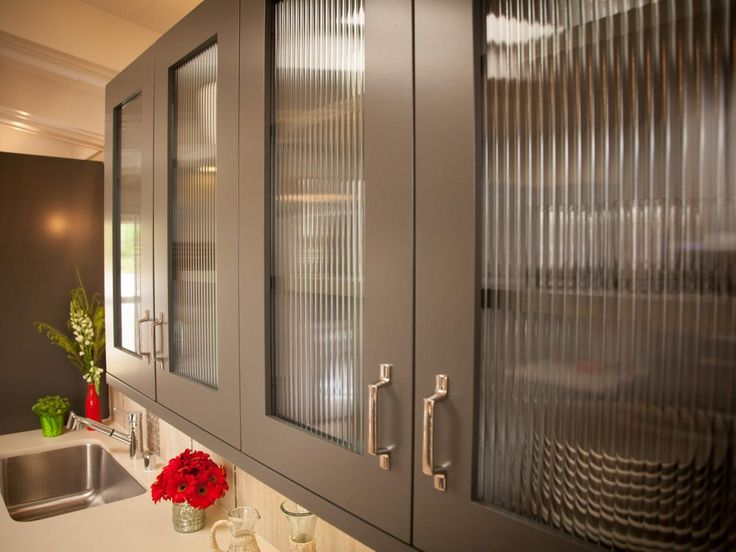 The glass doors on these gray kitchen cabinets lend a modern feel to this  kitchen.