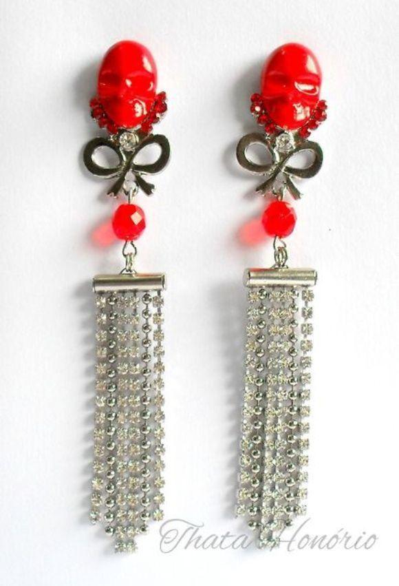 Cód: BN227 <br>TAM: 11,5 cm <br> <br>Brinco prateado com chaton de caveira em resina vermelho, pedras de vidro vermelha e correntes de strass.