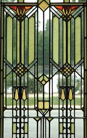 Stained glass window in a geometric design in green, yellow, and clear glass. - 1902 window by Henry Webster Tomlinson reflects the Prairie School philosophy of providing ornamentation while retaining a view through the window