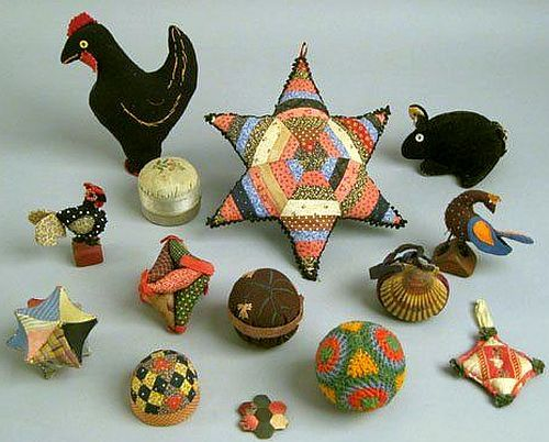 Group of old needlework pin balls and pin cushions.