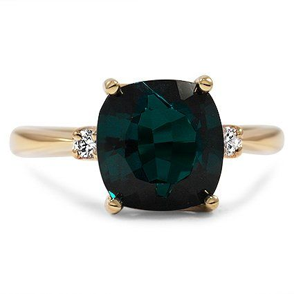 The Elinor Ring,  a cushion cut tourmaline with a deep bluish green hue, accented by two twinkling diamonds alongside it