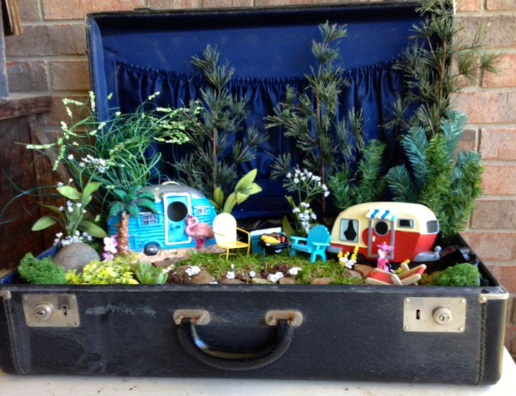 "This year I'm making various Fairy Gardens in containers.  This old black suitcase with blue lining seemed just right for my campers to set up in.  Have added a few ""real"" succulents to add to the garden area...hope they survive!"