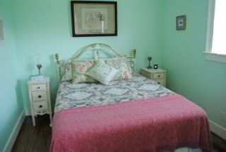 """Original Leahaven master bedroom with mint green walls, rose bedspread, floral quilt, white shabby chic bedside tables, """"brass"""" bed."""