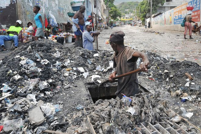 A man dug out a grate near a public garbage area in the south of Port-au-Prince, Haiti, April 10.