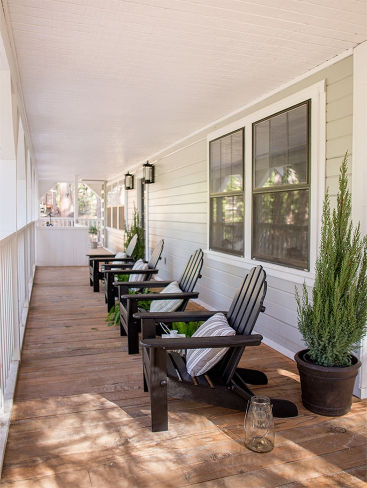 Black Adirondack chairs on a covered porch/deck