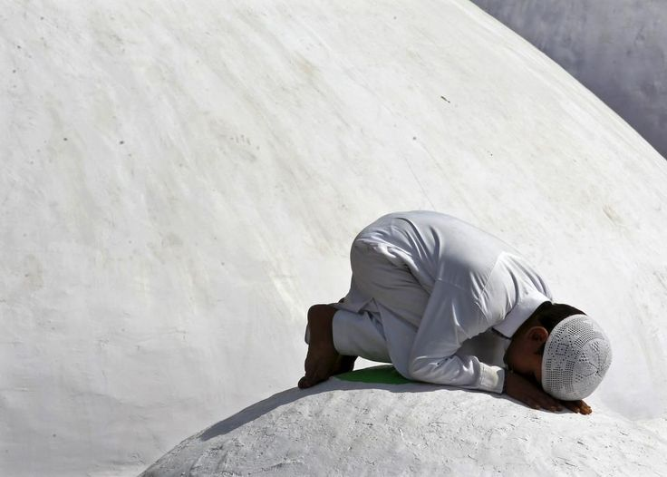 A Muslim boy offers a special prayer at a shrine on the eve of the Eid al-Adha festival on the outskirts of Ahmedabad, India, September 24, 2015. Muslims across the world are preparing to celebrate the annual festival of Eid al-Adha or the Feast of the Sacrifice, which marks the end of the annual haj pilgrimage, by slaughtering goats, sheep, cows and camels in commemoration of the Prophet Abraham's readiness to sacrifice his son to show obedience to Allah. REUTERS/Amit Dave