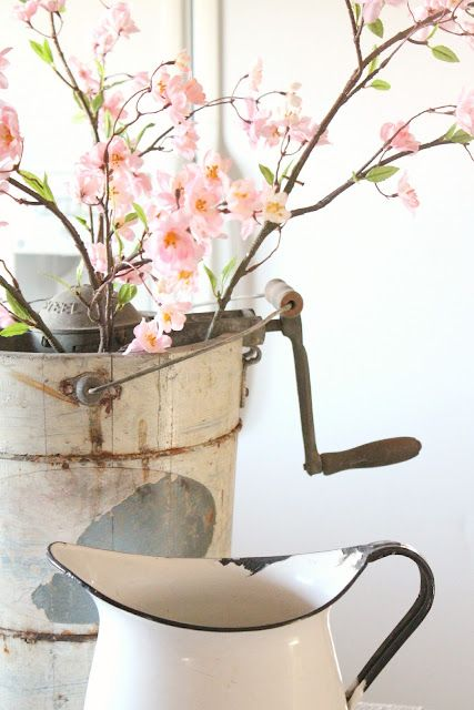 an old ice cream maker with faux flowers from Hobby Lobby- thanks to rusty hinge