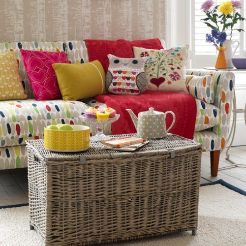 Multicoloured sofa with colourful cushions and ratten chest