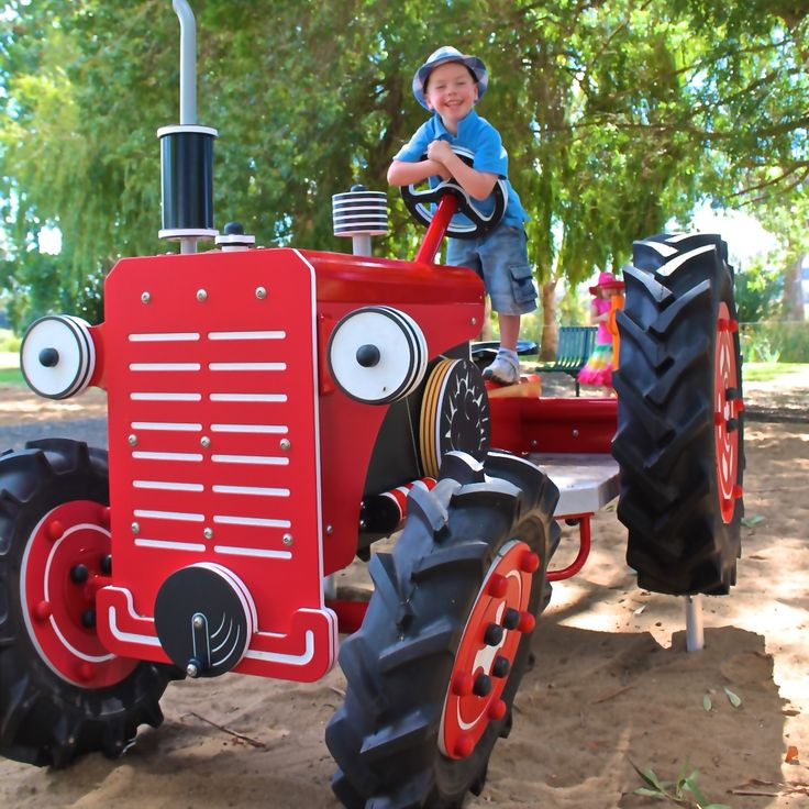 Let's be honest here, you would be smiling too if you discovered a lifesize tractor at a playground #Tractor #CustomDesign #Largerthanlife #exciting #ImaginativePlay #littlefarmer #countryside #RuralTheme