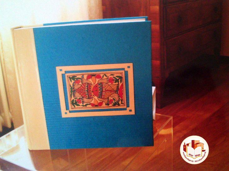 Album portafoto con dorso in similpelle bianca e piatti in carta blu, con disegno centrale. Realizzato da noi: www.rilegoerileggo.org