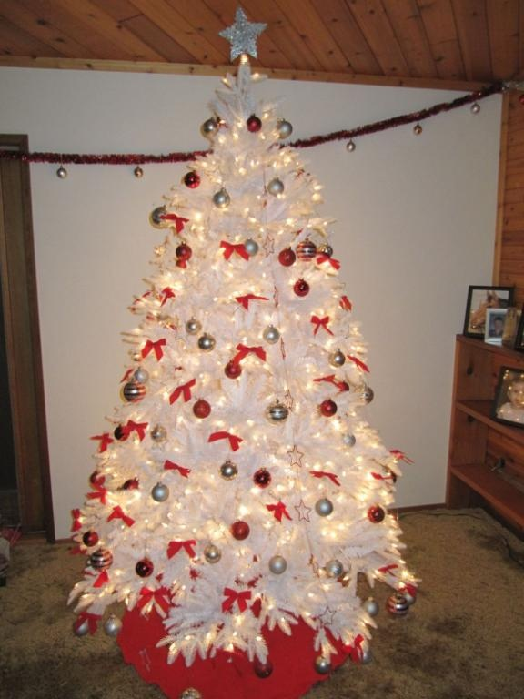 a a white christmas tree with red and gold decorations