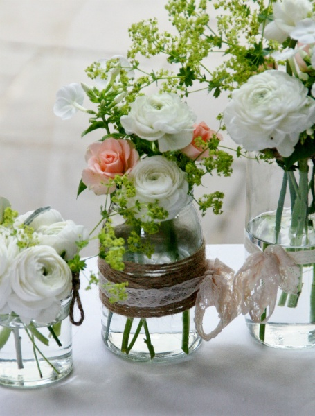 Jam jars with seasonal flowers and twine and lace detail. I bet this could be really simple to pull off!