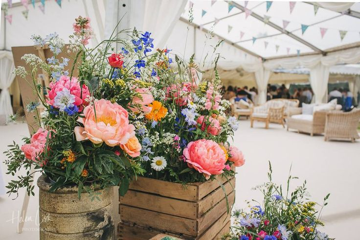 Clear roofs make this reception area of the wedding marquee a light and airy space....flower boxes and bunting bring colour and a country feel to the marquee.
