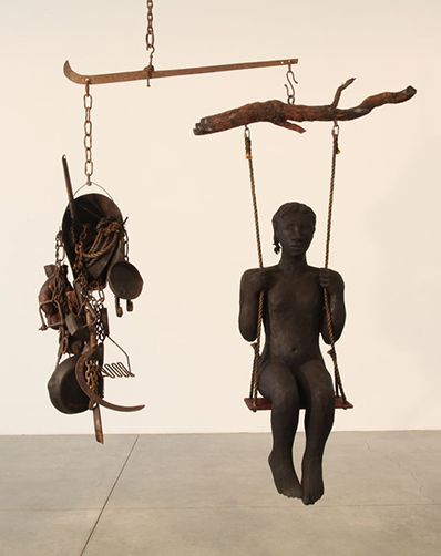 Allison Saar. American artist. In Weight , a young girl sits on a swing attached to a scale for weighing cotton. On one side is this taut little soul, pigtailed, carved in wood and sheathed only in a gleaming skin of coal dust; on the other, a cornucopia of cast iron tools of domestic and field labor (skillet, scythe, shears, chains), the implements that will determine her functional worth.