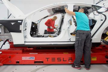 Workers add seat belts to a Model S sedan at Tesla's assembly plant in Fremont, Calif.