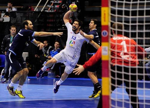 France's centre back Nikola Karabatic (C) vies with...
