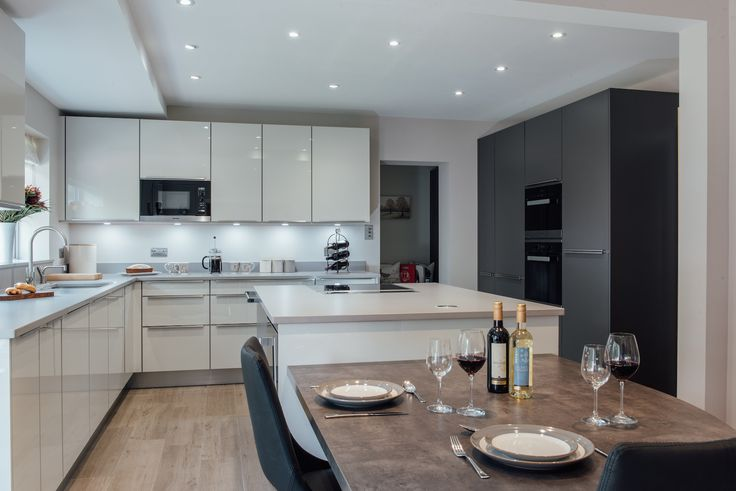 Storage space is often crucial when designing an open plan living space, such as this kitchen diner by Raycross Interiors - banks of cupboards that also hide integrated appliances can be a sleek and contemporary solution for a clutter-free look