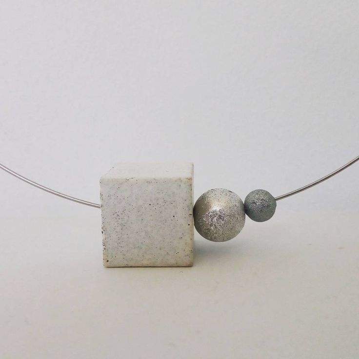 Concrete cubic bead, on minimal style necklace.