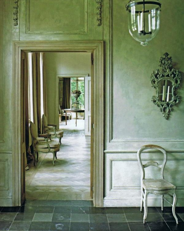 Le grande vestibule, sparsely adorned with a chaise d'époque,  19th century chandelier and mirrored sconce…has a tantalizing view through a succession of rooms…  stone giving way to aged parquet patterns underfoot Trouvais Blog