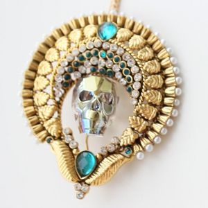 Named after the Mayan god of storms, the Chaac necklace represents your unshakeable strength and past victories.  It's a complete one-off. Handmade using Swarovski elements skull as a centre piece wearing an ornate headpiece incrusted with white and ocean green gems edged with pearl like beads. #necklace #statement #jewellery #skull #wearableart