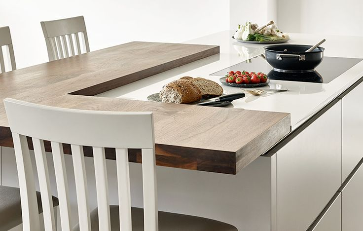 Split level island with adjoining breakfast bar in American black walnut. Modern Handle-less drawers finishing in Cornforth White by Farrow and Ball. Island with integrated hob.