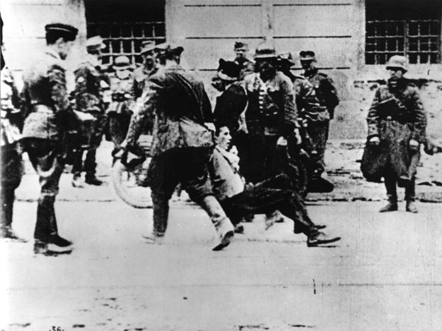 Warsaw, Poland, SS soldiers dragging a Jew in the street during an aktion in the ghetto.