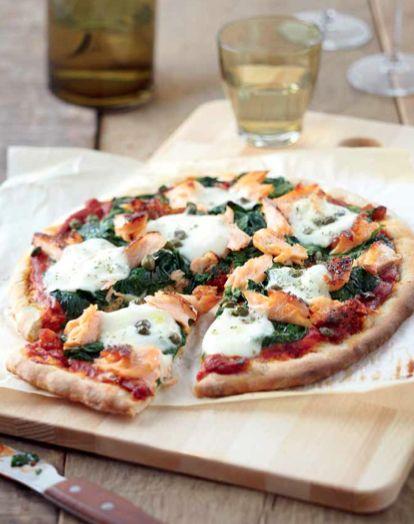 Pizza al salmone - Scongela il salmone e sminuzzalo. Riscalda il forno a 200°. Riscalda l'olio in padella con uno spicchio d'aglio. Aggiungi gli spinaci e saltali finchè saranno appassiti. Lasciali scolare. Taglia la mozzarella a pezzetti. Ricopri una teglia con carta da forno e disponi sopra le basi per la pizza. Distribuisci sulla pizza: salsa di pomodoro, spinaci, salmone, mozzarella e capperi. Spolverizza con origano, peperoncino e un filo d'olio. Cuoci in forno per 12-15 minuti.