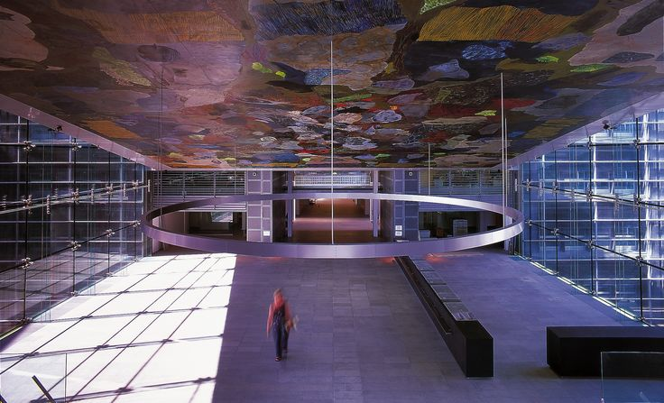 At the Royal Library in Copenhagen we were fortunate to work alongside the acclaimed artist Per Kierkeby.  positively enhance the sense of connection that we were trying to create. Here, Kierkeby suspended a large circular canvas floating above the information desk, a painting that announces the transition between old and new. #architecture #art #copenhagen #denmark