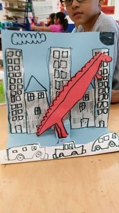 """Tracy Triplett's Kindergarten art projects inspired by the book If Dinosaurs Came Back To Life """"We read the book. Folded blue paper""""almost in half"""" Talked about cities and cityscapes. Added buildings with old phone book pages. Draw dino. Trace w marker. Cut. I cut the pop out paper slits for them. Glue dinosaurs on pop-outs. End of day one. Let dry. Trace buildings and add windows, clouds, etc. Draw cars on folded piece of paper, cut off top so only the cars are showing. Glue in front of…"""