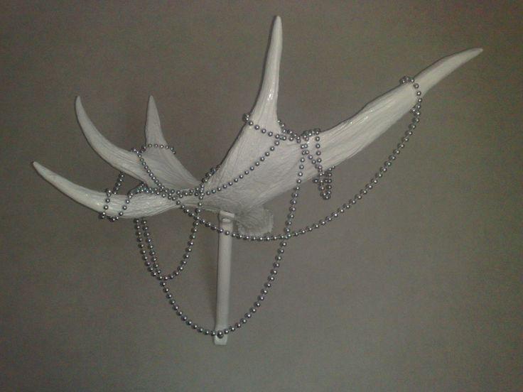 Hirven sarvet maalattiin valkoiseksi ja laitettiin hopeista helminauhaa roikkumaan