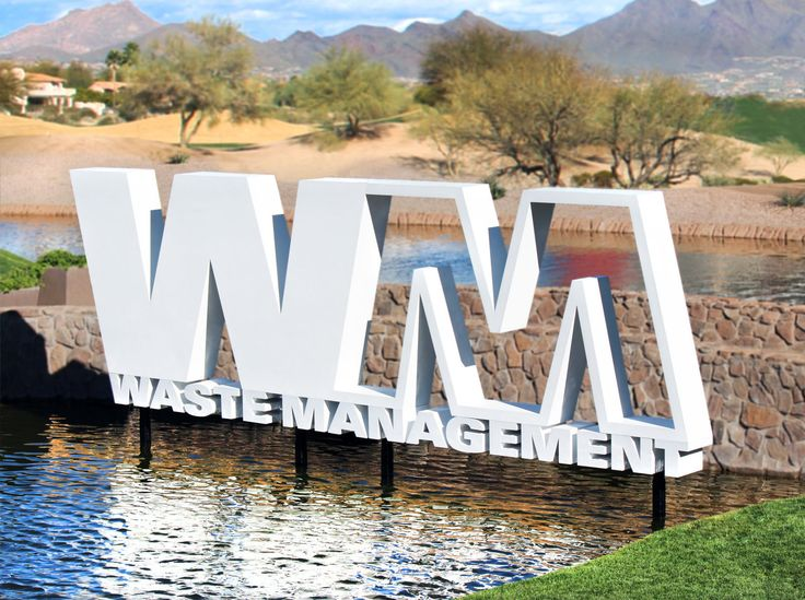 An over eight foot tall Waste Management logo brands the TPC Scottsdale's 15th hole. Custom designed steel engineering supports the aluminum logo above the water.