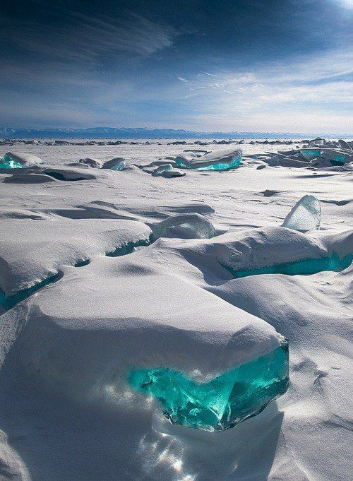 """""""In March, due to a natural phenomenon, Siberia's Lake Baikal is particularly amazing to photograph. The temperature, wind and sun cause the ice crust to crack and form beautiful turquoise blocks or ice hummocks on the lake's surface."""" this looks incredible!:"""