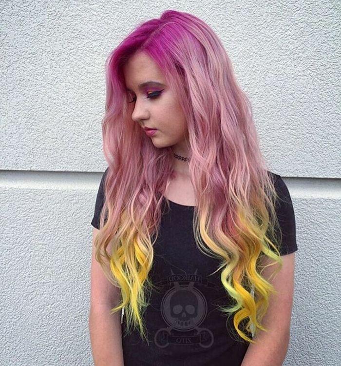 Teenager-Mädchen mit langen lockigen Haaren in drei Farben - pinker Ansatz mit langen Strähnen und gelben Spitzen, die leicht gelockt sind, sie trägt ein schwarzes T-Shirt mit Totenkopf-Print und einen schwarzen Chocker, ihre Augen sind pink geschminkt
