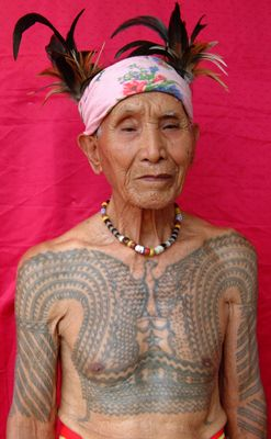 Lakay Dilag wears a very intricate bikking or warrior's chest tattoo. Traditionally, these V-shaped markings represented the gayang or eagle: an oracle bird and messenger to the Creator God Kabunian. However, this once abstract motif has been accentuated and replaced with a figurative rendition of the eagle that many WWII Kalinga veterans borrowed from peso or centavo coin designs from the American commonwealth period (1935-1946). The star (bituwon) beneath the eagle symbolizes the beacon…