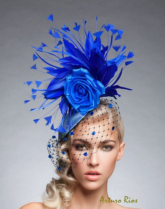 From my new Collection here is this Beautiful fascinator.  Made on a round base covered with light blue/green and royal blue pints, Embellished with black Russian netting with royal blue velvet dots, Goose and turkey feathers and a Royal blue silk rose. it includes a thin black elastic to secure it around your head.  All my headpieces are hand made to order , please allow a week while we make it, if this is a rush order, please contact me to make sure we can make it on time.  Thank you :...