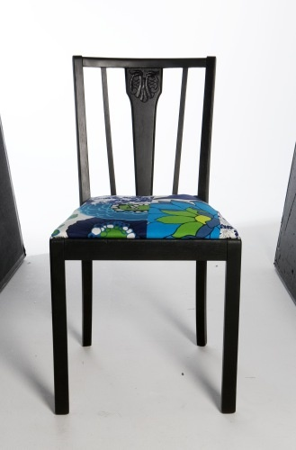Dining chair is painted with matte black spray paint, and seat re-upholstered with a fabric piece sewn of mixed, colorful fabric remnants