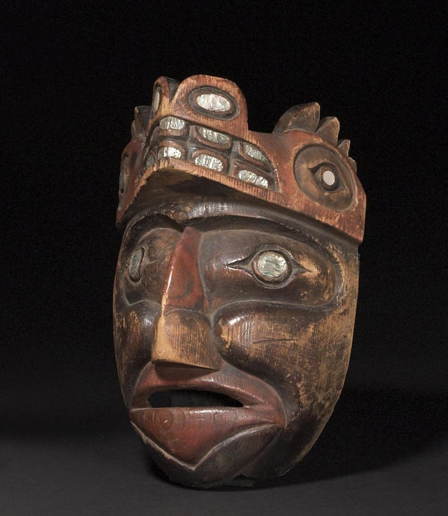 A Nootka mask  Carved with broadly defined facial features, the recessed eyes inset with abalone discs, wearing a Sisiutl headdress similarly embellished.  length 12in