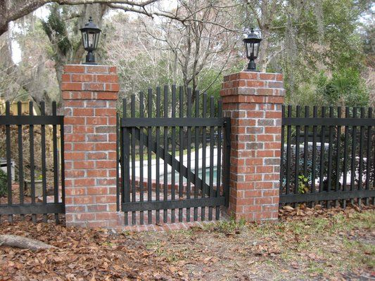 Red brick pillars with charcoal grey iron/or painted pickets
