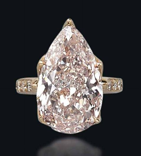 A COLOURED DIAMOND RING Set with a fancy light pink pear-shaped diamond, weighing approximately 11.67 carats, to the pavé-set diamond openwork gallery and shoulders, mounted in gold