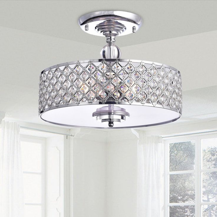 The Martina Chrome Finish Crystal 3-light Flush Mount Chandelier features a chrome finish, with a base and shade made of iron. 3-light set-up allows for a clean, complete look with lots of illumination.